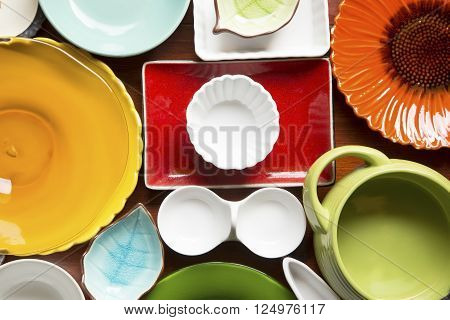Colorful dishes and utensils on a wooden background