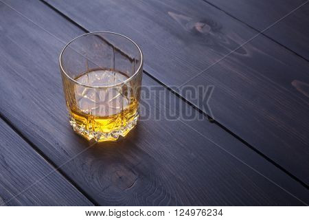 Tumbler glass with whiskey on a dark wooden surface