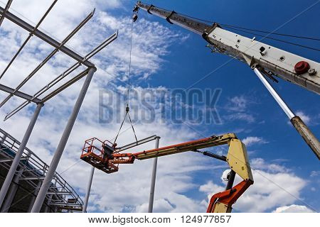 Height worker is helping to the mobile crane to place part on building skeleton.