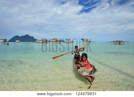 SEMPORNA, MALAYSIA - APRIL 17, 2015 - Bajau laut paddling a boat to the shore. The Bajau Laut have for centuries lived out their lives almost entirely at sea.