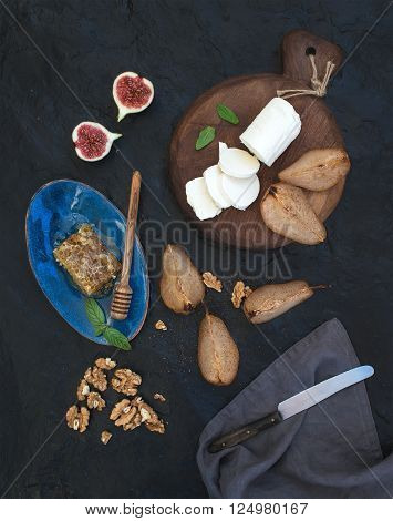 Appetizer set. Roasted pears, goat cheese on rustic dark wooden board, fig, honey and walnuts over black stone background, top view