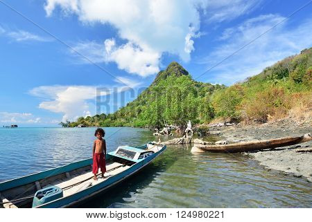 SEMPORNA MALAYSIA - APRIL 18 2015 - Bajau laut kid on a boat in Bohey Dulang island shore. The Bajau Laut have for centuries lived out their lives almost entirely at sea.