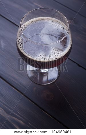 Goblet glass with dark beer on a dark wooden surface