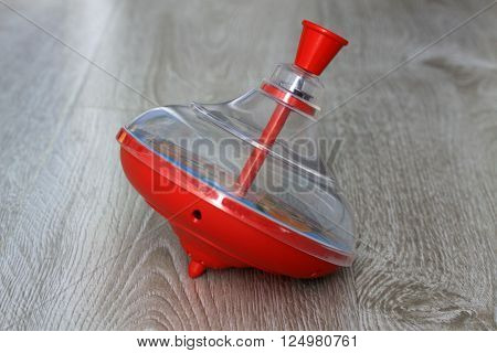 Red plastic whirligig on the wooden floor