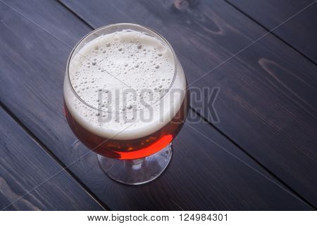 Goblet glass with amber ale on a dark wooden surface