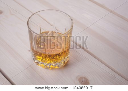 Tumbler glass with whiskey on a light wooden surface