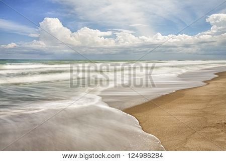 Waves breaking gently on a sandy beach with a cloudy blue sky above are captured with a longer exposure showing motion in the surf.