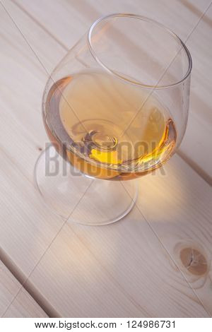 Snifter glass with brandy on a light wooden surface