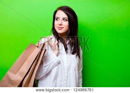 portrait of the beautiful young woman with shopping bags on the green background