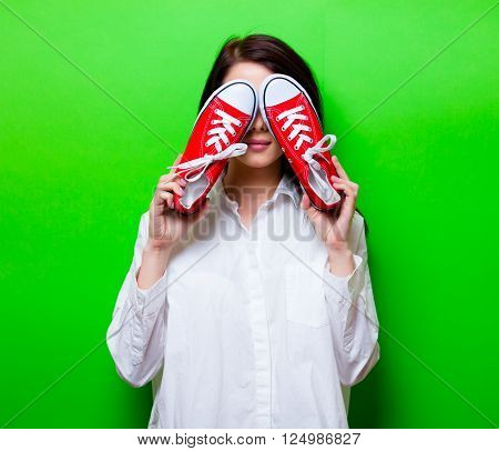portrait of the beautiful young woman with red gumshoes on the green background