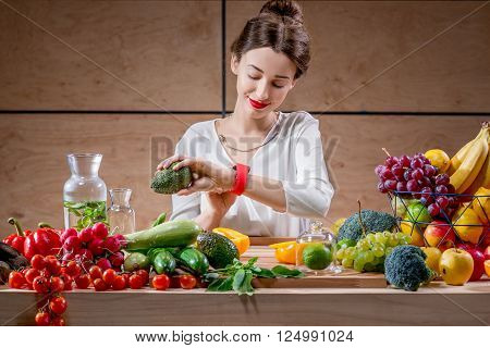 Young and pretty woman watching smart watch sitting at the table full of fruits and vegetables in the wooden interior. Counting calories with smart watch app. Food and health care concept