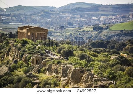Tourists visiting old Greek temple Concord at valley of temple, the world heritage site on Sicily island, Italy