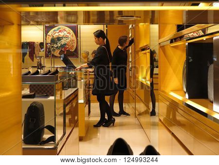 PADUA ITALY - CIRCA NOVEMBER 2014: stylish fashion shop in the city centre displaying high couture clothes with Asian shop assistant