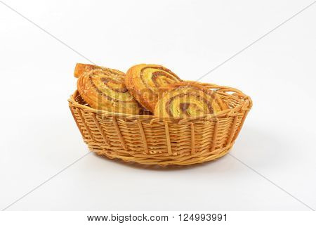 basket of sweet cinnamon rolls on white background