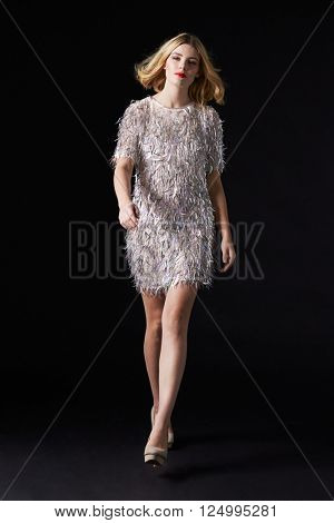 Glamorous blonde woman walks toward camera, black background