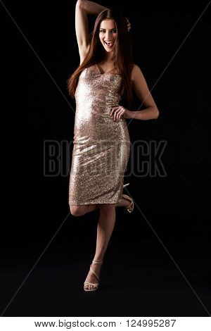 Young woman in evening dress standing on one leg, vertical