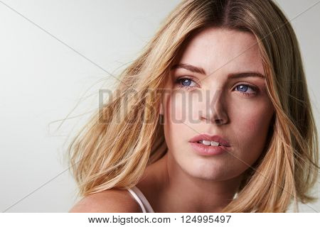 Blonde woman looking away, hair blowing, close-up horizontal