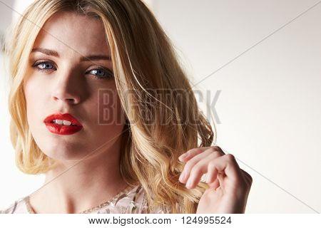 Glamorous blonde woman with hand raised, horizontal portrait