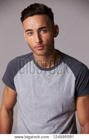 Vertical waist up studio portrait of serious young man