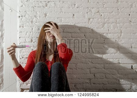sad and worried pregnant teenager girl or young desperate woman holding positive pink pregnancy test looking scared and devastated at home floor in unwanted baby and unexpected motherhood