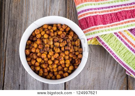 Roasted spicy Seasoned Chick Peas healthy snack on wooden table