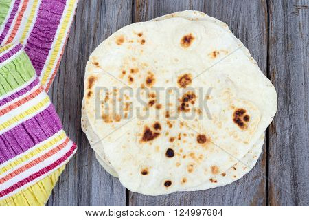 Homemade Naan Flatbread pile on wood table