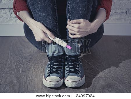 unidentified faceless woman sitting on the floor holding positive result pregnancy test
