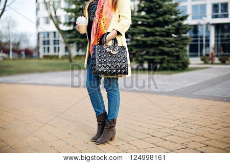 close-up portrait of a fashionable young lady posing in the city, accessories, spring shoes, perfect feet, the spring collection of boots, stylish gray ankle boots, fashionable yellow coat, black bag, coffee