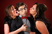 stock photo of hottie  - Two aggressive cougar women corner a shy young man - JPG