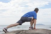 picture of stretching exercises  - Runner doing stretching exercise on a rock at the sea - JPG