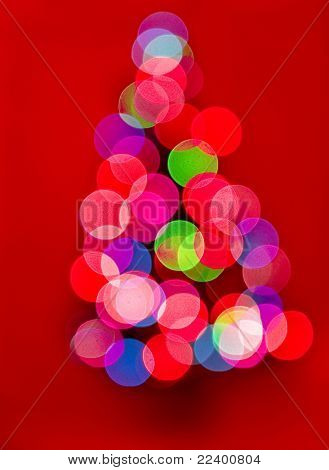 Christmas tree with defocused lights on red background