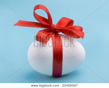 White egg wrapped around with red ribbon bow over blue background