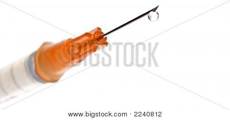 Orange Syringe/Needle With Drop Of Liquid On The Tip