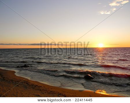 Sunrise on a sandy beach with waves