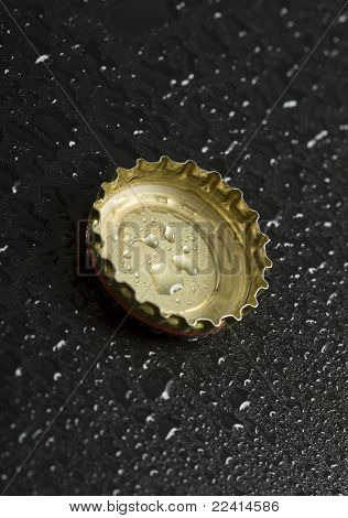 bottle cap with water droplets on black