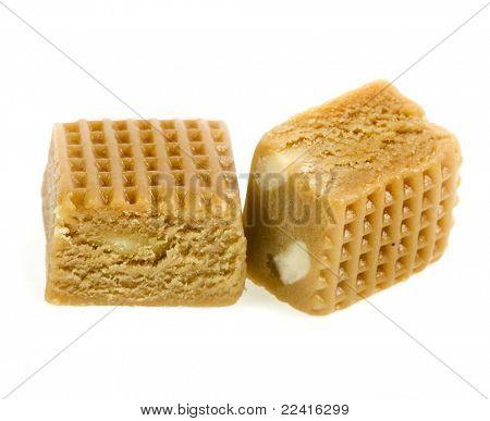 crema caramelo cubo con tuercas aislado sobre un fondo blanco