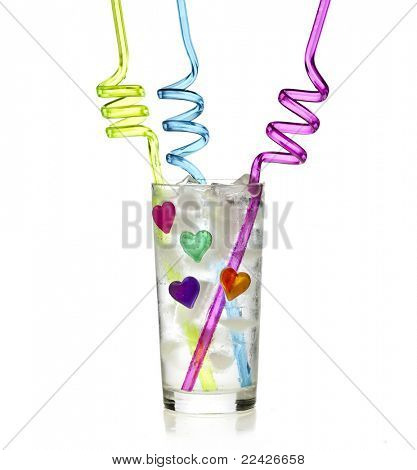 Glass of soda water with ice cube and colorful curly drinking straw isolated on white