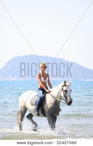 Young female riding her horse in the sea in Greece