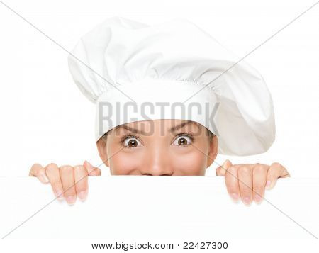 Chef Sign. Woman cook / baker looking over paper sign billboard. Surprised and funny expression on young Asian / Caucasian woman isolated on white background.