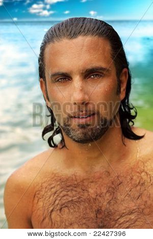 Close up portrait of a man on the beach with wet hair