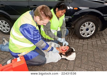 Paramedics checking a woman injured during a car accident (the sleeve badges have been replaced by a non existing logo)