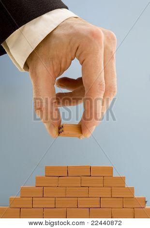 businessman building a bricks wall pyramid