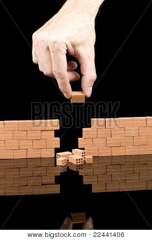 hand putting bricks on a broken wall isolated on black background