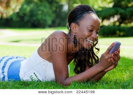 Teenage Black Girl Using A Phone, Lying On The Grass