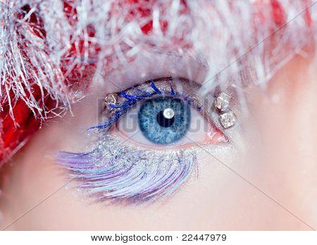 concepto de maquillaje de invierno en el ojo de la mujer azul en el pelo plateado de azul y rojo