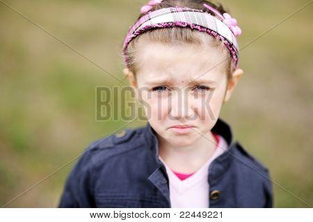 Cute child girl makes upset weepy face