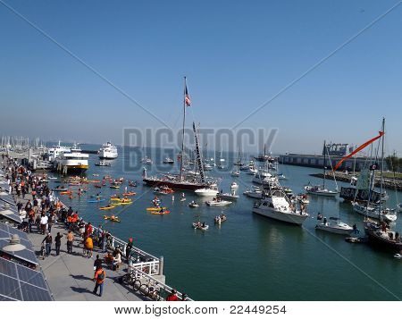 People Walk Along Promenade With Boats Filling Mccovey Cove