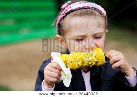 Menina bonita criança comer um milho cozido ao ar livre