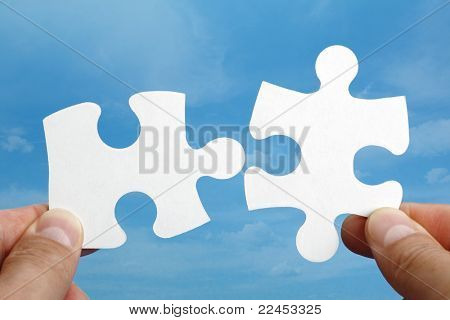 Holding two jigsaw pieces of a blank puzzle trying to fit together against blue sky background