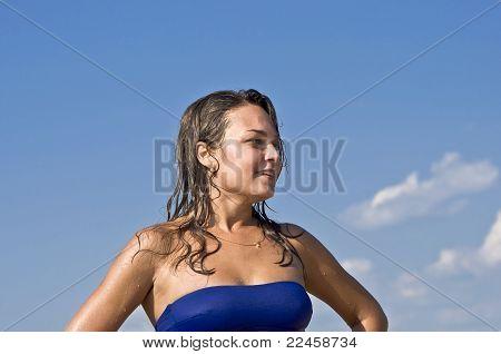 mulher de biquíni, sorrindo para o céu azul